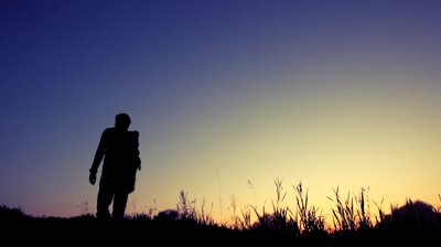 stock-footage-silhouette-of-man-with-rucksack-walks-uphill-against-sunset-sky-from-camera